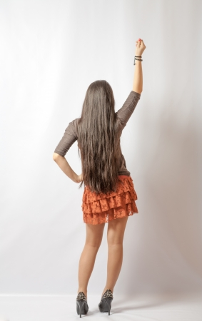 Backview of japan girl gesture on gray in studio back view pointing full body shot photo