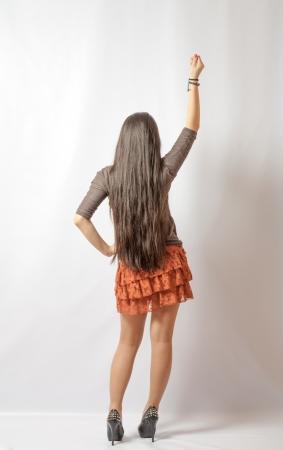 backview: Backview of japan girl gesture on gray in studio back view pointing full body shot Stock Photo