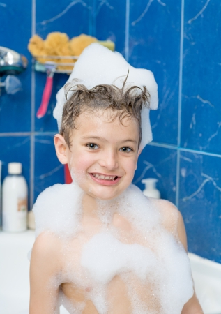 Smiling little boy front view  Kid covered with soap bubbles against a blue wall in bathroom photo