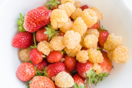 a whole bunch of raspberries and blueberries in close up photo