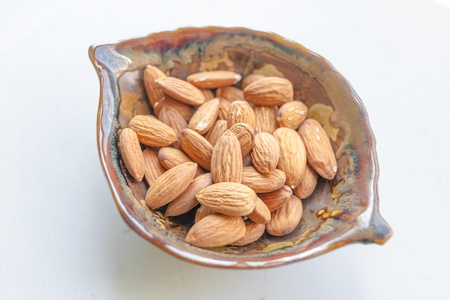 Almonds  bowl full of almond nut on white with shadow  Almonds in a bowl photo