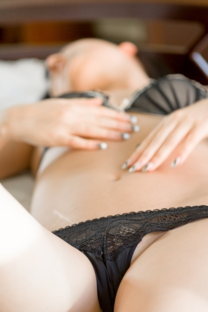 femme en sous vetements: belle femme brune en lingerie sexy couch�e dans son lit Banque d'images