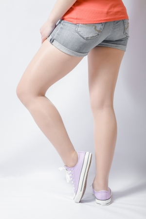 Long woman legs on white pink gumshoes on side view photo