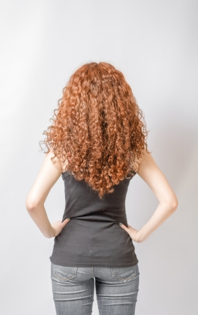 woman back: Back view of young woman in jeans and  black shirt points at wall. Rear view Stock Photo