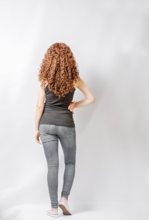 specifies: Back view of young woman in jeans and  black shirt walking  Rear view