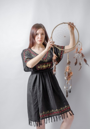 Indian squaw girl in traditional Indian wear and dream catcher posing to the camera   版權商用圖片