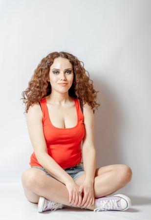 curly hair brunette on white background weared orange red shirt positive girl joy concept sitting in lotus meditation photo