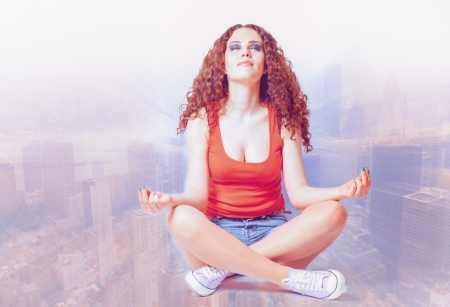 young woman do yoga meditation against blurred cityscape her eyes closed cross process toned photo
