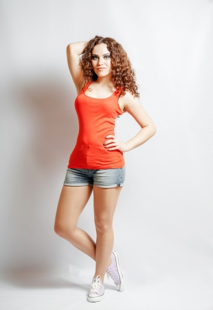 curly hair brunette on white background weared orange red shirt positive girl joy concept looking at camera photo