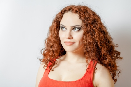 20 24 years old: curly hair brunette on white background weared orange red shirt positive girl joy happyness concept