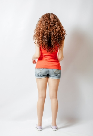 Back view of young woman in red shirt  Rear view full body shot photo