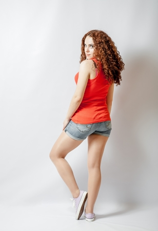Back view of young woman in red shirt looking at camera  Rear view full body shot photo