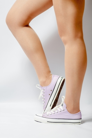 Long woman legs on white pink gumshoes on side view Stock Photo - 19194549