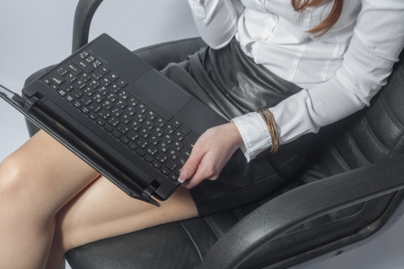 Beautiful young woman working with a laptop in the room on lap closeup photo
