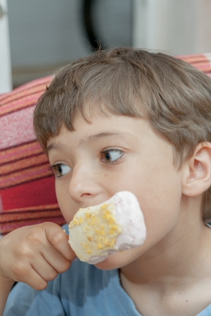 Cute little boy eating chocolate ice cream indoors photo