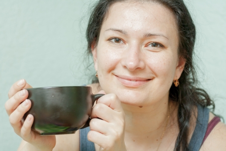Close-up of a beautiful girl with a cup near the face photo