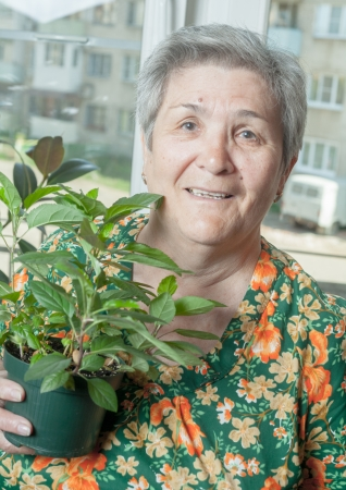 Portrait of smiling senior woman holding flower pot houseplant photo