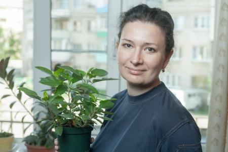 average: Woman holding flower pot, with houseplant Stock Photo