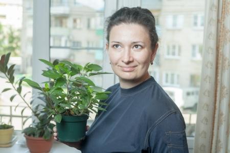 average woman: Latino Woman holding flower pot, indoor houseplant