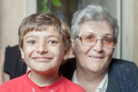 portrait of a senior woman and her grandson indoors photo