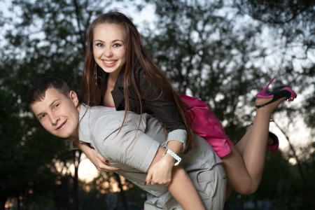 Young loving couple piggybacking in the park in the evening sunset photo