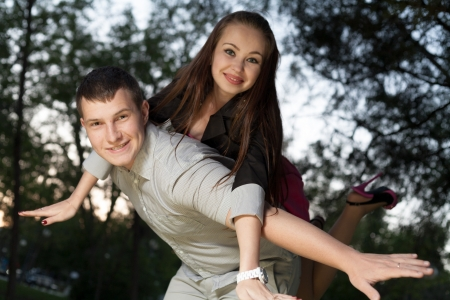 Young loving couple piggybacking in the park in the sunset closeup photo