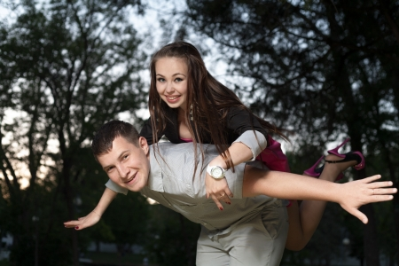 Young loving couple piggybacking in the park in the evening sunset Stock Photo - 19505045