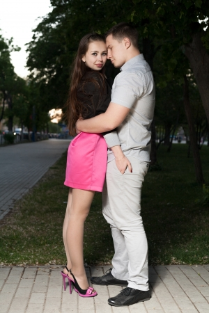 Young couple in love - young man embracing his girlfriend outdoors  Full body shot in the dark photo