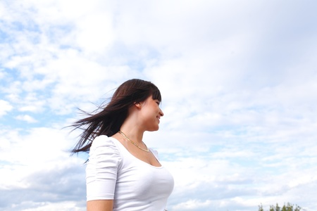 beautiful long hair brunette woman  aganst sky summer day portrait photo