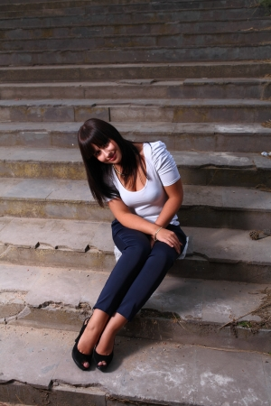 beautiful young woman outdoors on old stairs photo