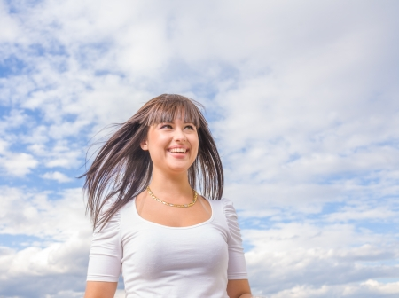 beautiful long hair brunette woman aganst sky summer day portrait