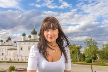 Model posing in front of tall historical building in old Russian style, torso shot photo