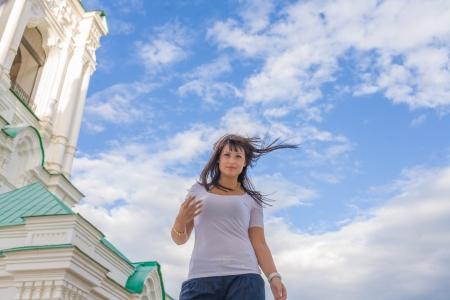 Model posing in front of tall historical building in old Russian style on wind photo