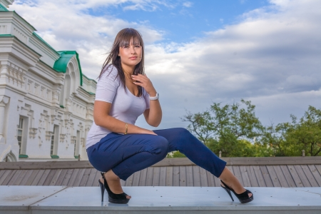 Model posing in front of tall historical building in old Russian style, full body sitting shot photo