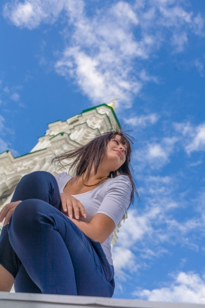 Model posing in front of tall historical building and blue sky photo