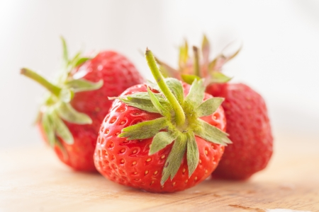three strawberries on wooden table photo