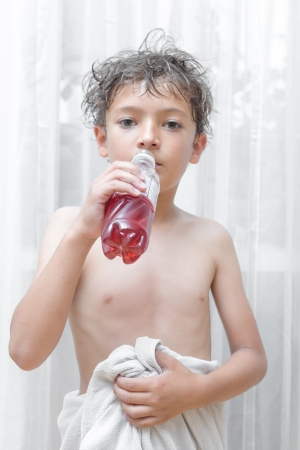 Little kid is drinking from bottle indoors, vertical shot Stock Photo