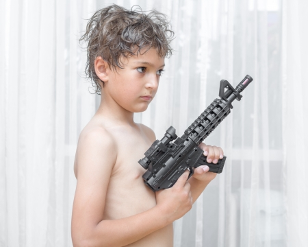 Portrait of little boy with automatic weapon on white background indoors photo