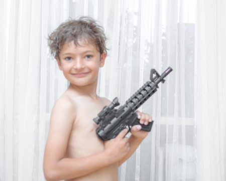 Portrait of little boy with automatic weapon M16 on white background indoors photo