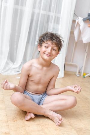 position d amour: Garçon assis sur le plancher méditer Yoga Lotus Position Banque d'images