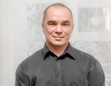 ハンサムな白人 40 代男黒の t シャツに灰色の背景に笑みを浮かべて肖像画