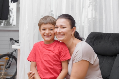 Happy mother and son smiling at home photo