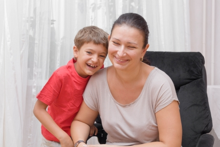 Mom and son having fun indoors  Happy mother and little son in the living room photo