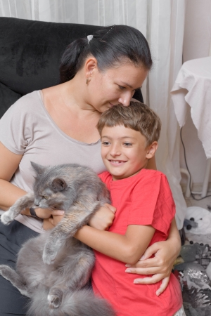 mother and son with cat in the living room having fun photo