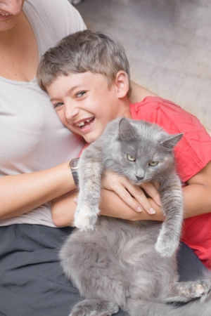 mother and son with cat having fun indoors photo