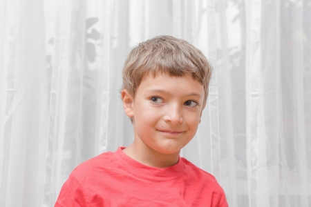 Smiling happy boy in red T-Shirt shot indoors on a light background  photo