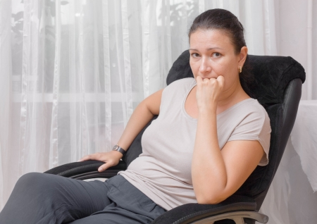 Young woman sitting on chair indoors thinking photo