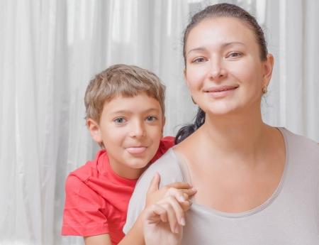 lengua afuera: Madre feliz con la lengua hijo sobre fondo claro en interiores, en la sala de estar Foto de archivo