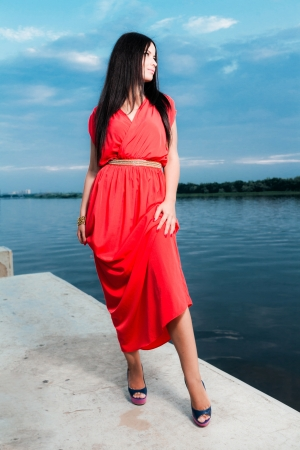 Fashion portrait of classy brunette in red shiny dress and long straight hair . photo