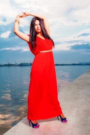 Fashion portrait of classy brunette in red shiny dress and long straight hair   photo